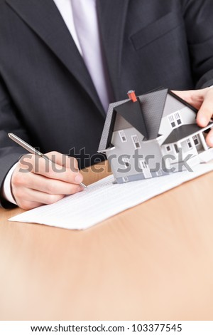 Real estate concept - business man signs contract behind household architectural model - stock photo