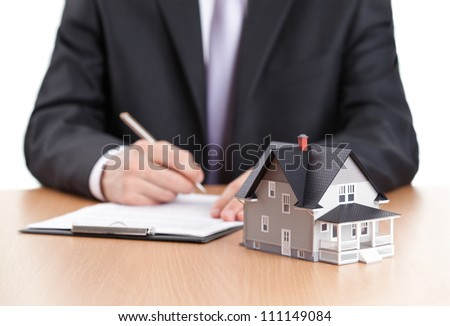 Real estate concept - businessman signs contract behind home architectural model