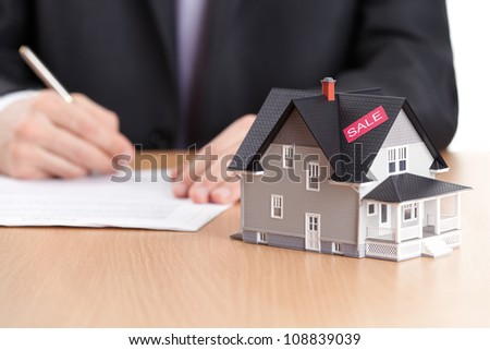 Real estate concept - businessman signs contract behind household architectural model - stock photo