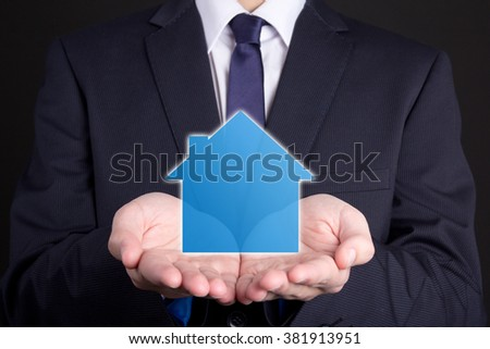 real estate concept - close up of business man holding small house in his hands - stock photo