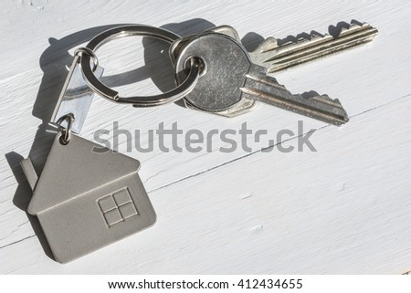 Real estate concept. Close up of keys on white wooden sunny background.  - stock photo