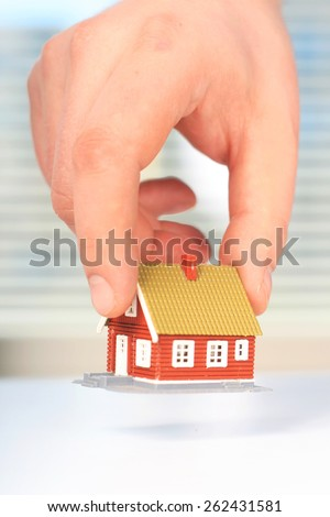 Real estate concept. Hand is giving a house. - stock photo