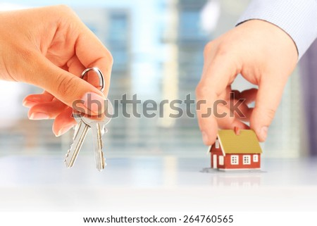 Real estate concept. Hand with key and new house. - stock photo