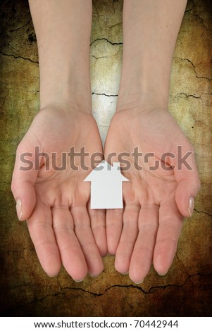 Real estate concept. hands holding a paper house icon