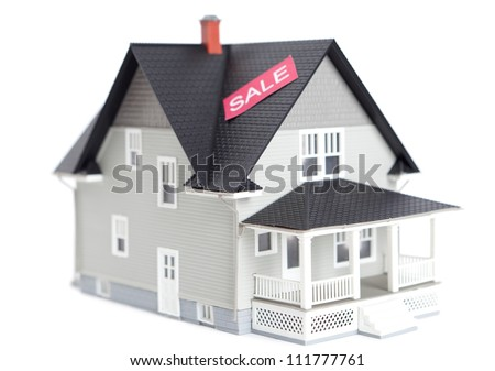 Real estate concept - home architectural model with sale sign, isolated - stock photo