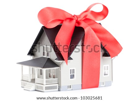 Real estate concept - house architectural model with red bow on it, isolated - stock photo