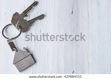 Real estate concept - Key ring and keys on white wooden background - Copy space - stock photo