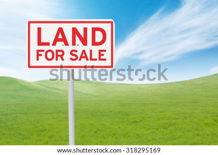 Real estate concept. Land For Sale signboard on the meadow under clear sky - stock photo