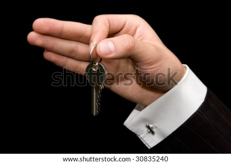 Real estate concept: Man giving the keys of new apartment or office - stock photo
