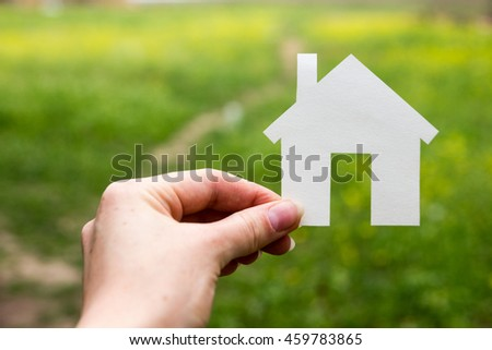 Real Estate Concept, model house on green grass field flower backdrop. Workplace, Architectural project. Construction background.