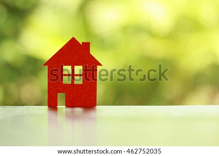 Real Estate concept.Orange paper home on green nature blur background.