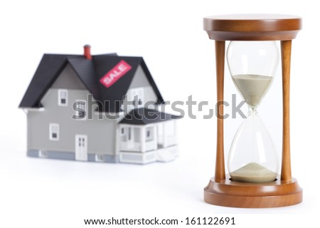Real estate concept - sandglass in front of house architectural model, isolated - stock photo