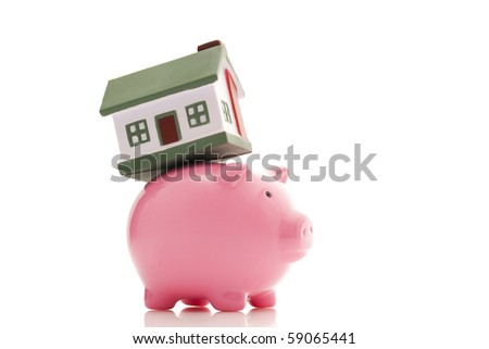 real estate concept; small house on a piggy bank - stock photo