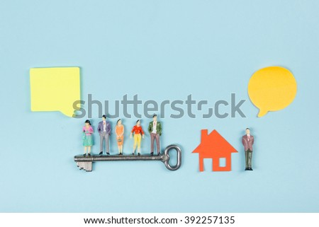 Real Estate concept. Speech bubbles and people toy figures Construction, building. Paper model house with key on blue background. Top view. Copy space for text. - stock photo