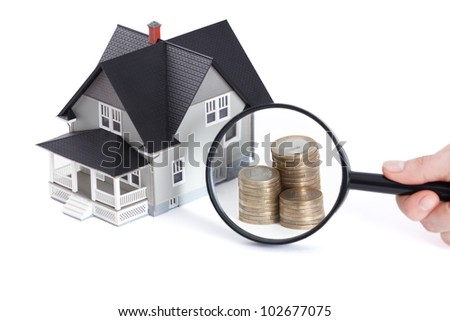 Real estate concept - stacks of coins in front of house architectural model, isolated - stock photo