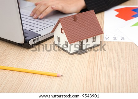 real estate concept with a house and office desk, shallow dof