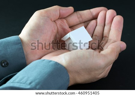 Real estate concept with realtor holding a model house in his hands