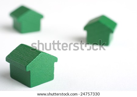 Real estate conceptual image with house tokens over a white surface - stock photo