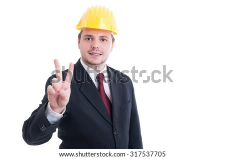 Real estate contractor or architect showing peace and victory gesture wearing suit, tie, and yellow hardhat - stock photo