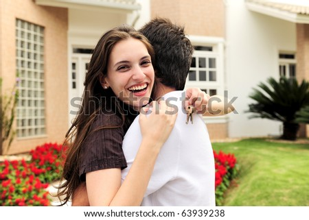 real estate: couple showing keys of their new house - stock photo