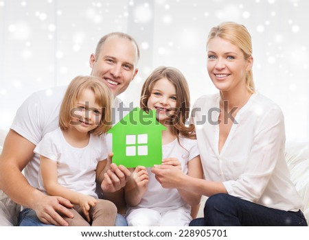 real estate, family, people and home concept - smiling parents with two little girls holding green paper house - stock photo
