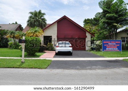Real Estate For Sale Open House Welcome Sign on front yard lawn of Suburban Back Split Snout Garage style Home Parked Car Blue Sky Clouds - stock photo