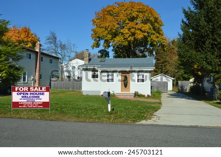 Real estate for sale open house welcome sign on front yard lawn of Suburban bungalow home sunny autumn clear blue sky day residential neighborhood USA - stock photo