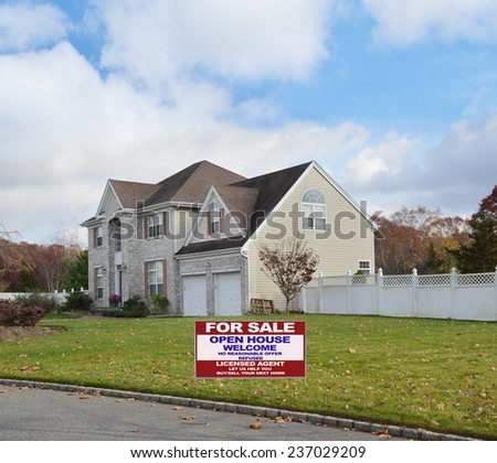 Real Estate for sale open house welcome sign Suburban brick McMansion style home with two car garage white picket fence residential neighborhood blue sky clouds USA - stock photo