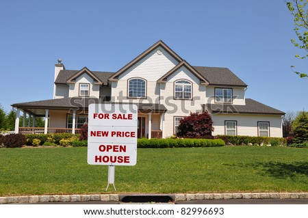 Real Estate For Sale Sign on Lawn of Large Suburban Home Residence on Sunny Day