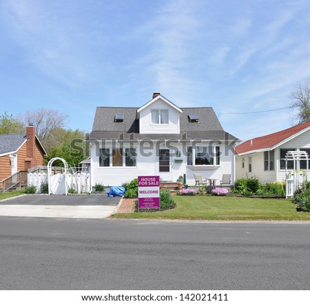 Real Estate For Sale Sign Suburban Bungalow Home Sunny Blue Sky - stock photo
