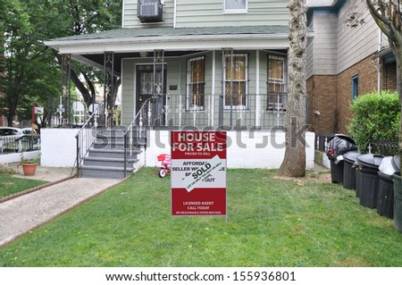 Real Estate For Sale Sold Sign front yard lawn home lined with black plastic trash cans USA