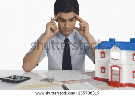 Real estate holding head and sitting near a model home - stock photo