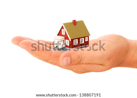 Real estate. House in hand isolated over white.