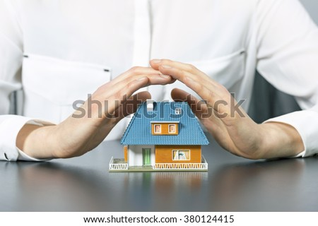 real estate insurance concept - human hands saving small house - stock photo