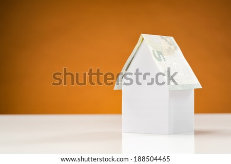 Real estate investment concept - a white paper house with a roof from a five Euro banknote, with orange background and copy space. - stock photo