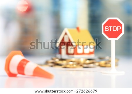 Real estate investment concept. House and money and stop sign.
