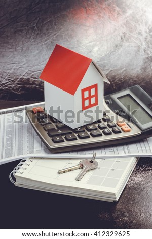 Real estate investment. House, key and calculator on table. Concept home loans - stock photo