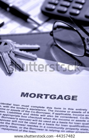 Real estate lending broker home mortgage loan document with keys and glasses on a financial banking lender agent desk (fictitious document with authentic legal language)