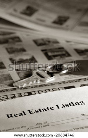 Real estate listing contract and key over newspaper open on house for sale classified section - stock photo