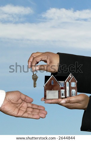 real estate market concept photo of a home sale shoeing african american hands transferring over the house and keys. Includes a clipping path. - stock photo