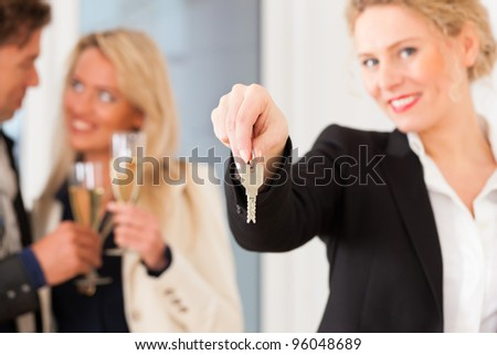 Real estate market - young couple looking for real estate to rent or buy; they celebrate with champagne and get the keys - stock photo