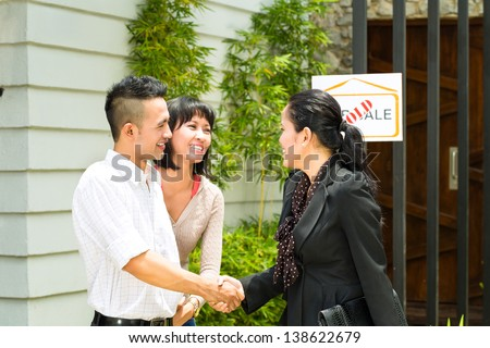 Real estate market - young Indonesian couple looking for real estate apartment or house to rent or buy, the realtor and the client shaking hands - stock photo