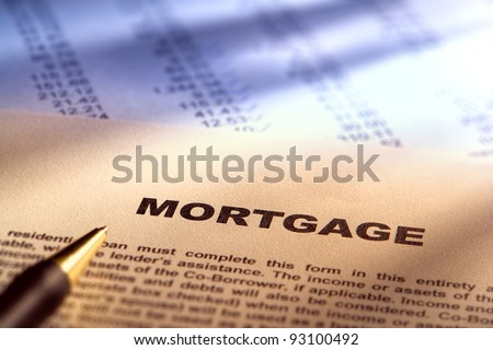 Real estate mortgage application document form over financial figures paperwork for a loan transaction lender approval processing and commitment with ink pen (fictitious document with legal language) - stock photo