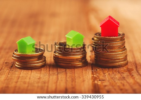 Real estate mortgage concept with small plastic house models on top of stacked coins. - stock photo