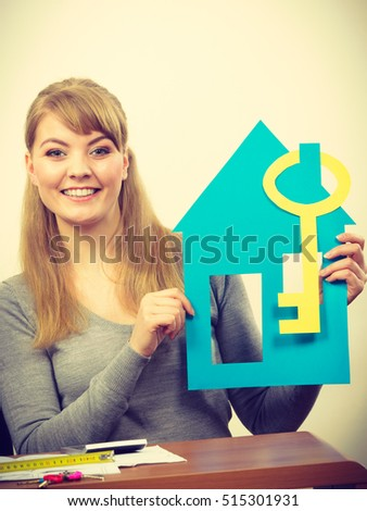 Real estate ownership finance concept. Young lady with house cutout. Woman holding home and key.