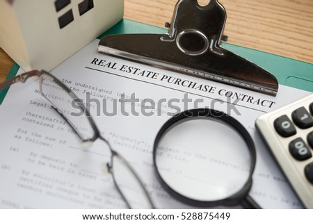real estate purchase contact with architectural model and calculator and magnifier