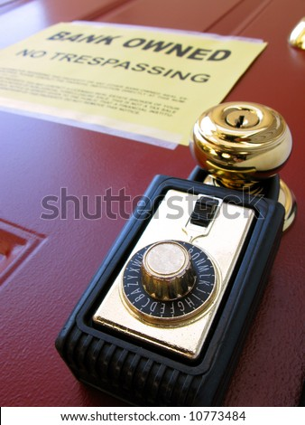 Real estate Realtor combination lock box on foreclosed house door with attached lender bank owned no trespassing foreclosure notice of repossession (fictitious document with authentic legal language) - stock photo