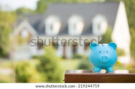 Real estate sale, home savings, loans market concept. Housing industry mortgage plan and residential tax saving strategy. Piggy bank isolated outside home on background. Focus on piggybank. Homeowner  - stock photo