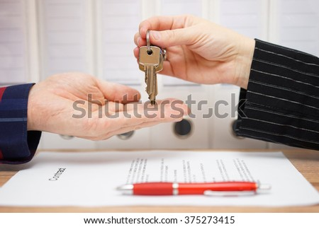 real estate seller is giving keys to buyer after signed deal - stock photo