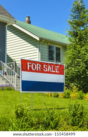 """Real Estate Sign """"For Sale"""" on front yard of a house. - stock photo"""